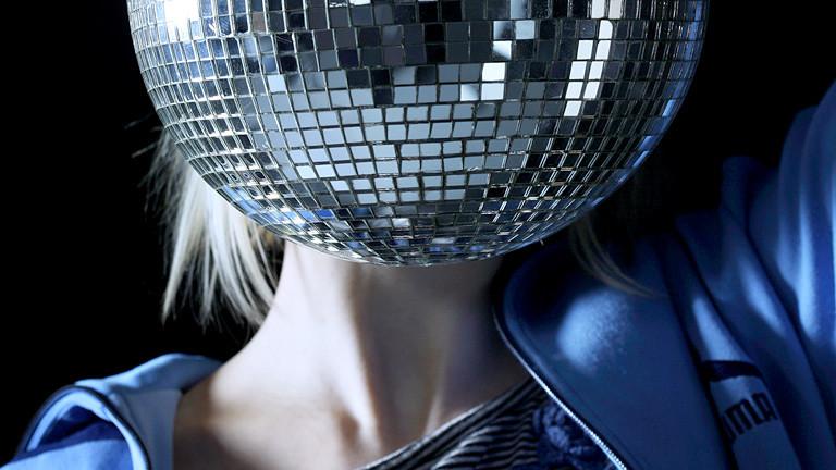 Frau mit Diskokugel vorm Kopf.
