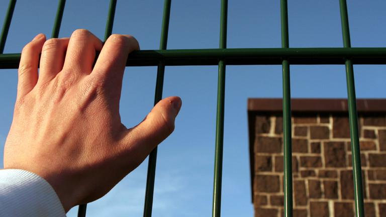 Eine Hand greift an einen Zaun, dahinter ist eine Mauer zu sehen