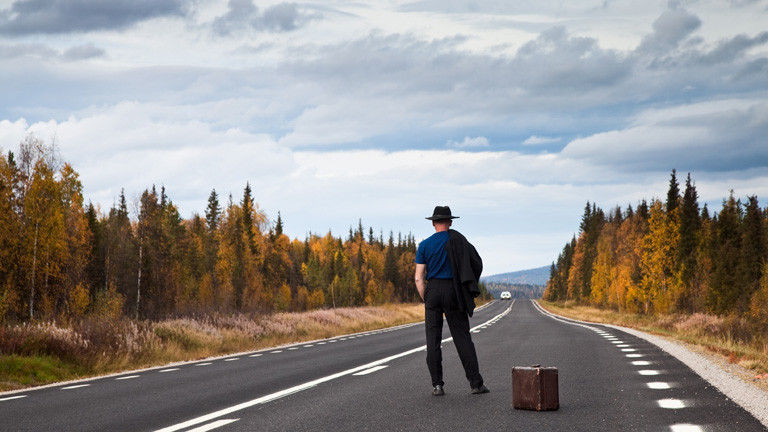 Ein Mann steht auf einer Landstraße und schaut in die Ferne