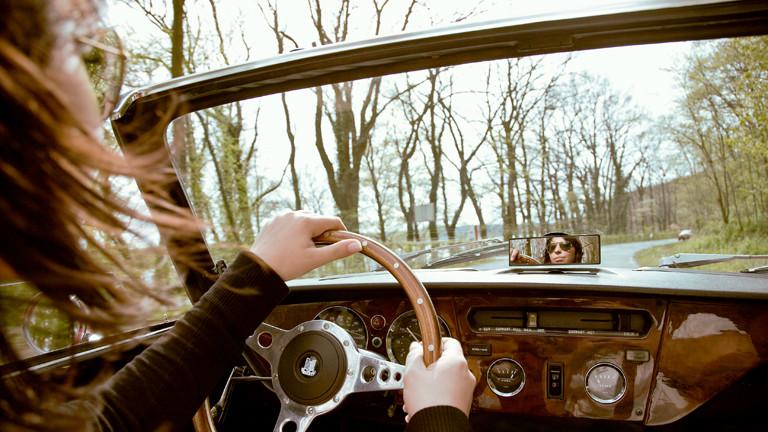 Eine Frau sitzt hinter dem Steuer eines Cabrios und fährt durch eine Allee