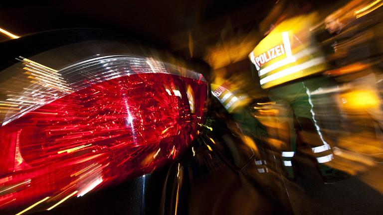 Verzerrtes Bild von Rücklichtern und einem Polizisten bei Nacht