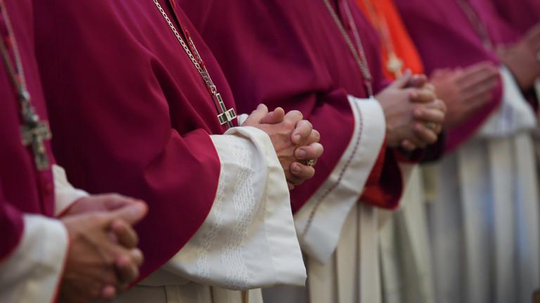 Bischöfe stehen in Gewändern in einer Reihe. Sie falten die Hände.