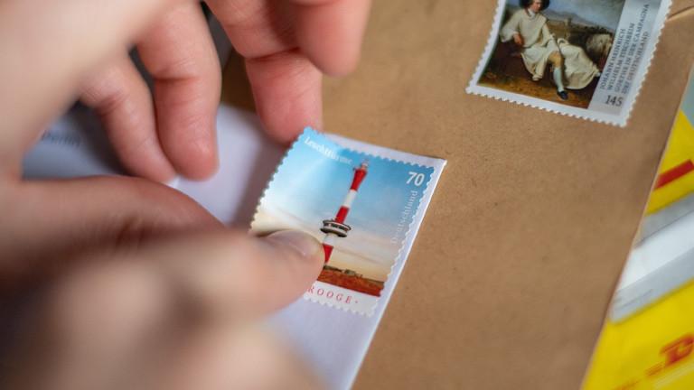 Hände kleben eine Briefmarke auf