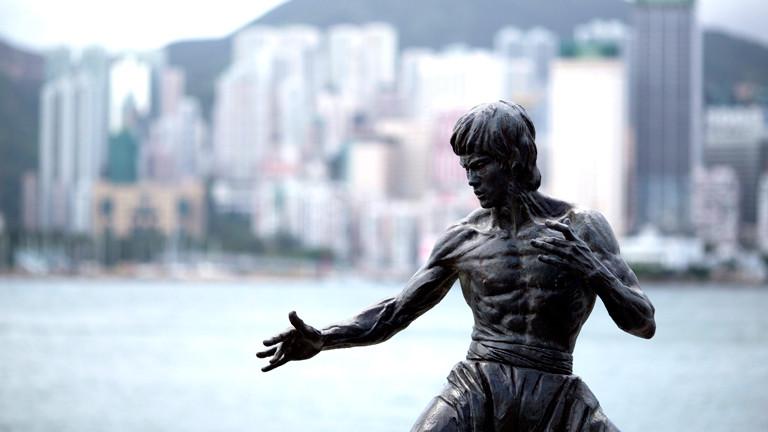 Die Statue von Bruce Lee vor der Skyline von Hongkong