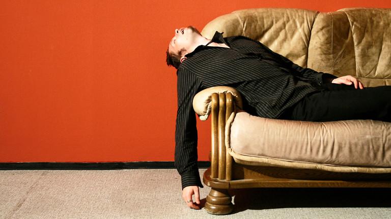 Ein Mann schläft auf einer Couch