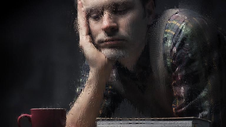 Ein Mann schaut traurig durch ein verregnetes Fenster