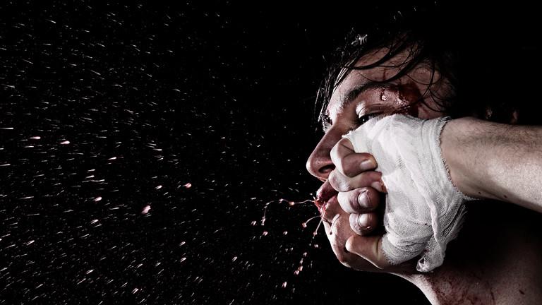 Ein Mann bekommt eine Faust ins Gesicht, es spritzt Blut.
