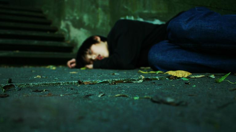 Ein junger Mensch liegt vor einer Treppe auf der Straße