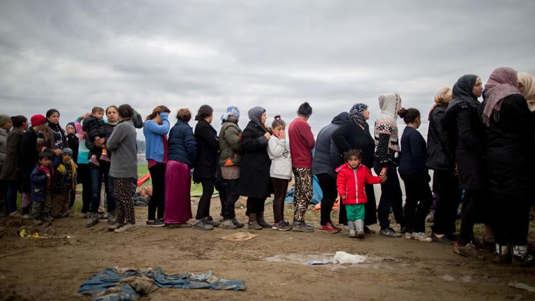Flüchtlinge stehen am 12.03.2016 im Flüchtlingslager in Idomeni an der Grenze zwischen Griechenland und Mazedonien im Schlamm für eine Kleiderspende an