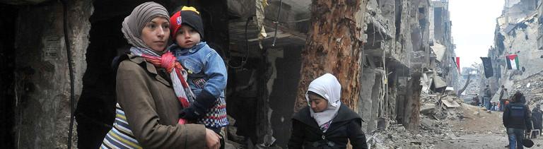 Drei Frauen mit Kindern auf dem Arm stehen in einer völlig zerbombten Straße im syrischen Yarmouk.