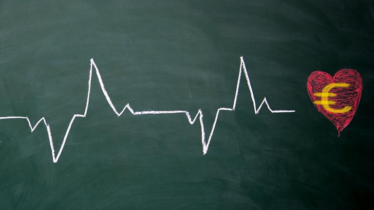 Die Herzschlaglinie eines EKG endet in einem auf eine Tafel gemalten Herzen. Auf dem Herz ist das Eurozeichen zu sehen...