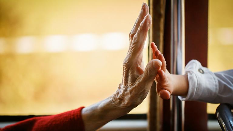 Eine alte Hand streckt sich einer Kinderhand entgegen