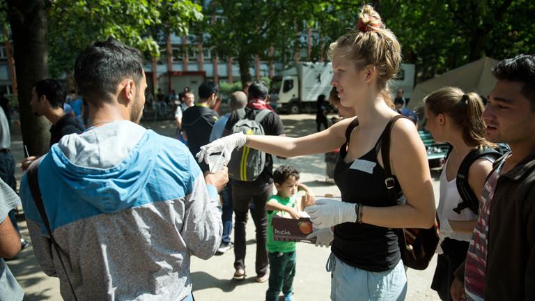 Eine Helferin verteilt Essen und Getränke am Berliner Landesamt für Gesundheit und Soziales