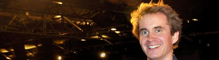 Henning Beck lächelt nach dem Erreichen des Science Slam Finales 2012