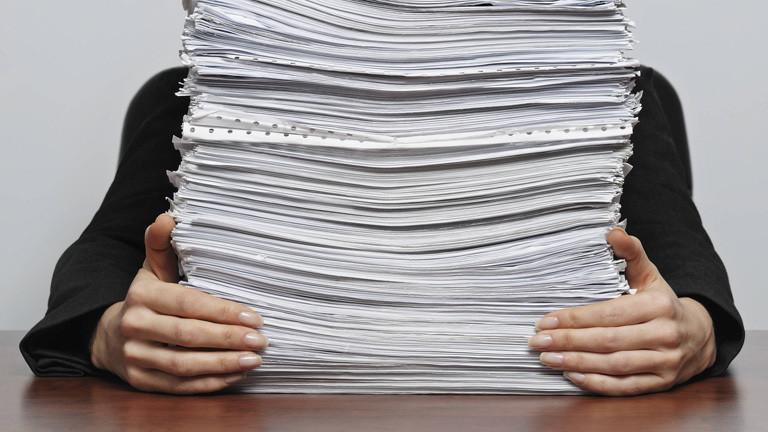 Person hinter einem Papierstapel