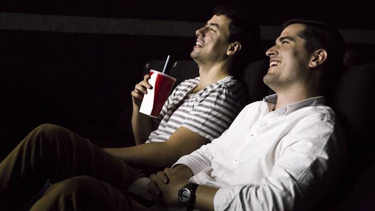 Zwei Männer im Kino - sie lachen.