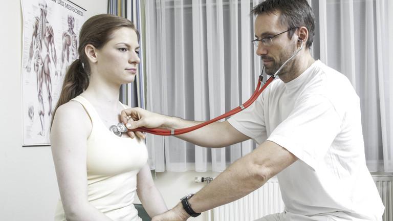 Arzt hört den Herzschlag einer Patientin ab