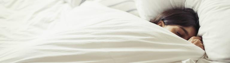 Frau liegt im Bett und zieht die Decke bis zur Nasenspitze