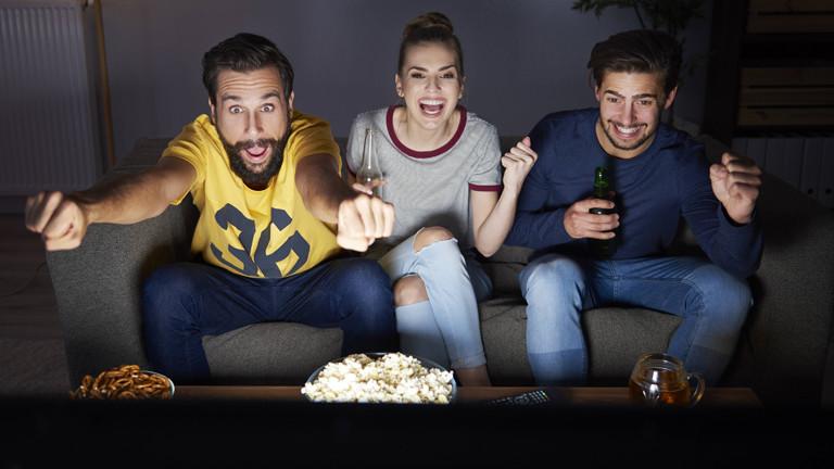 drei Menschen schauen Fußball auf einer Couch