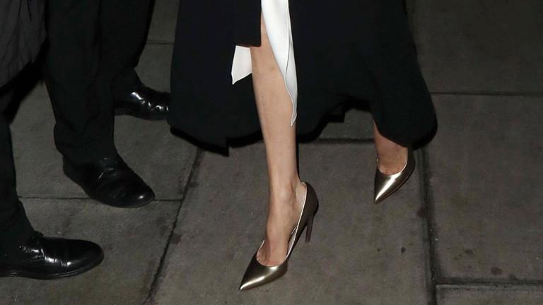 Frauenfüße in goldenen Pumps und Männerfüße in feinen schwarzen Lederschuhen.