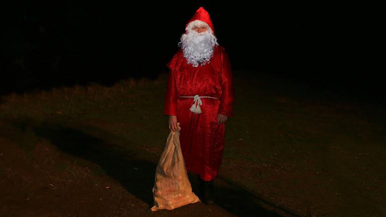 Ein Weihnachtsmann vor dunklem Hintergrund mit eine gelben Sack.