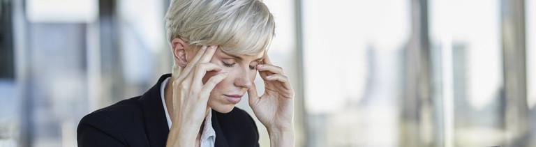 Frau im Büro, die sich die Schläfen reibt und gestresst aussieht