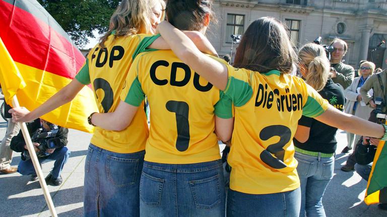 """Frauen mit Trikots, auf denen """"FDP"""", """"CDU"""" und """"Die Grünen"""" steht."""