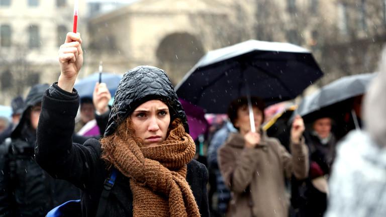 Passanten halten einen Stift in die Luft und demonstrieren im Regen stehend Solidarität mit den ermordeten Menschen beim Attentat auf die Redaktion von Charlie Hebdo.