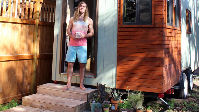 Ein Mann vor einem kleinen Holzhaus.
