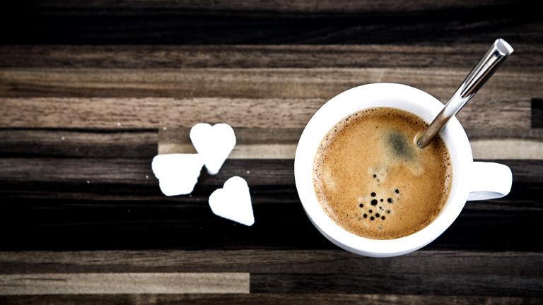 Eine Tasse Espresso, daneben Zuckerherzen