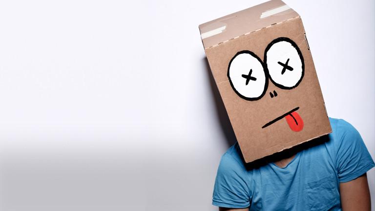 Ein Mann hat einen Karton über den Kopf gestülpt auf den ein Gesicht mit heraushängender Zunge gemalt ist.