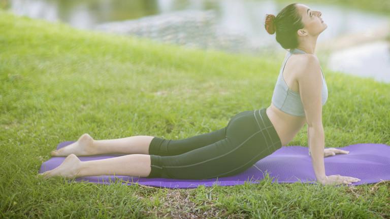 Frau bei einer Yogaübung auf der Wiese