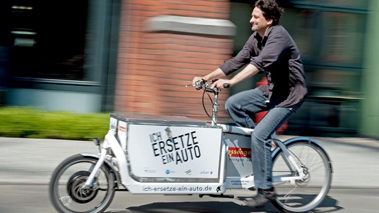 Mann mit einem Rad, das vorne einen Laderaum hat.
