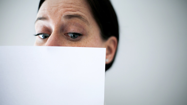 Frau blickt erstaunt auf ein Blatt Papier.