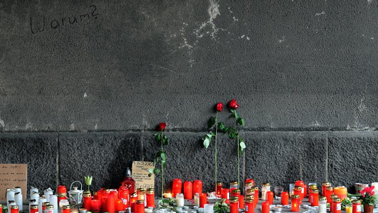 Blumen und Kerzen für die Opfer stehen an der Wand des Tunnels, in dem bei der Loveparade mehrere Menschen getötet wurde.