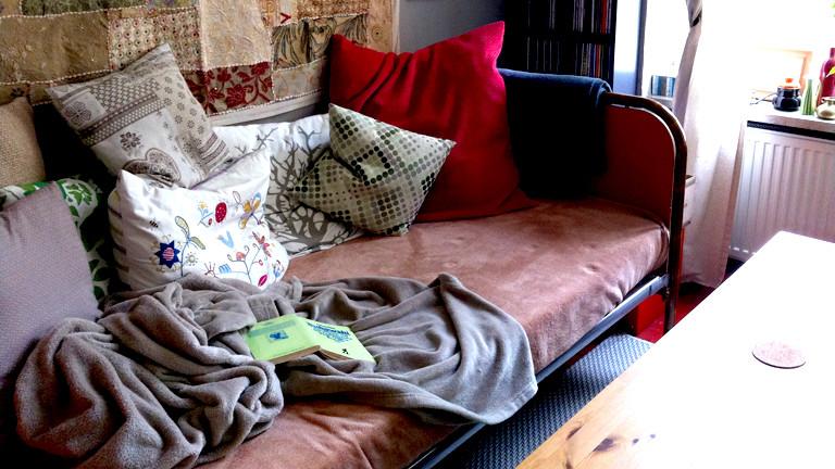 Auf einem alten Bett liegen zahlreiche Kissen