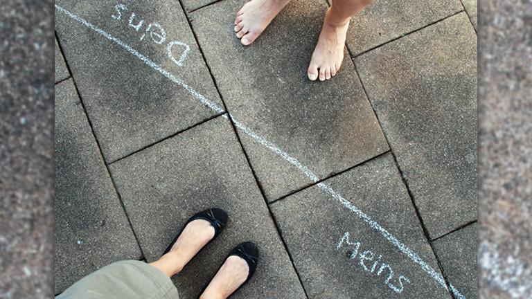 Ein Mann und eine Frau stehen sich gegenüber, zwischen ihnen eine Linie mit Kreide gezogen, auf der einen Seite steht meins, auf der anderen deins