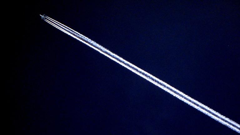 Ein Flugzeug hinterlässt am Nachthimmel einen Kondensstreifen