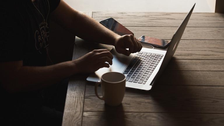 Mensch sitzt am Computer, neben ihm Kaffeetasse und Handys