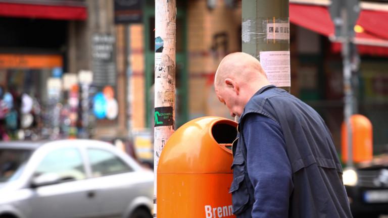 Ein Mann schaut in eine orange Mülltonne