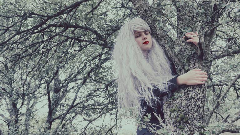 Frau mit geschlossenen Augen, die sich an einen Baum schmiegt, ausgeblichenen Farben.