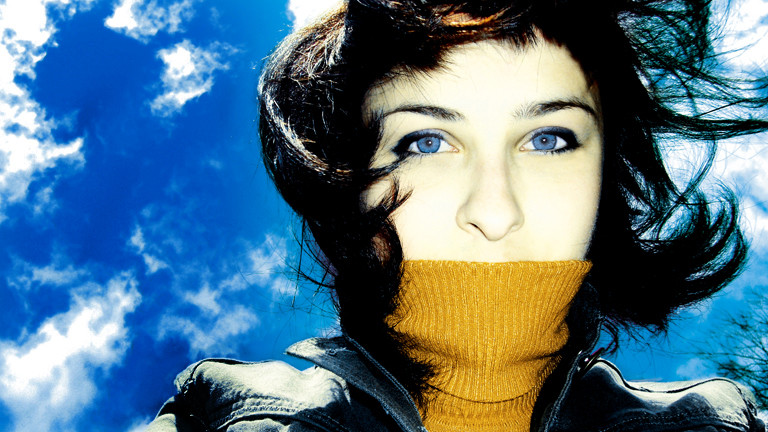 Eine Frau guckt von oben in die Kamera, hinter ihr ist der blaue Himmel mit kleinen Wölkchen zu sehen