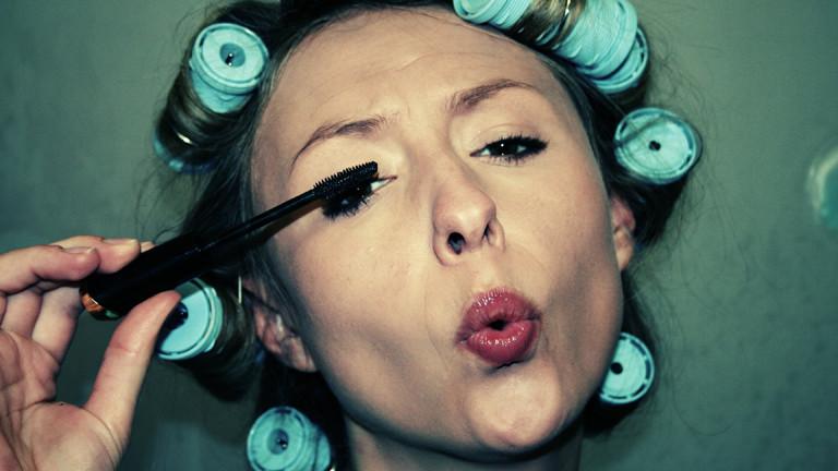 Frau, die ihre Wimpern tuscht und Lockenwickler im Haar hat