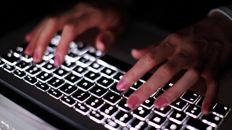 Frauenhände, die auf einer Tastatur tippen.
