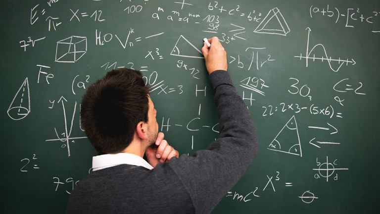 Mann steht an der Tafel und schreibt.