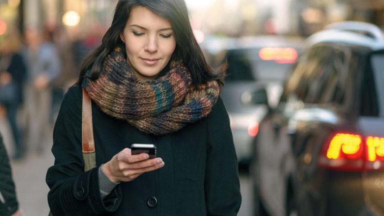 Frau auf der Straße mit Smartphone in der Hand