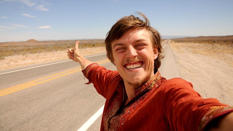 Raphael Fellmer steht grinsend am Straßenrand in einer ziemlich öden Gegend