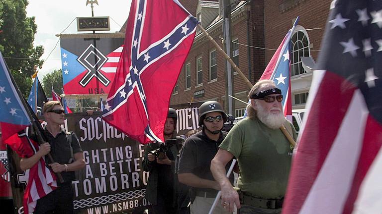Demonstranten mit USA-Fahnen und rechten Symbolen