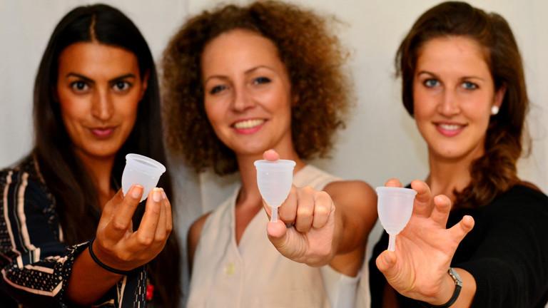 Die drei Gründerinnen von Ruby-Cup halten die Menstruationstassen ins Bild