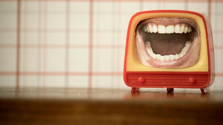 Ein Minifernseher auf dessen Bildschirm ein Bild von einem aufgerissenen Mund zu sehen ist